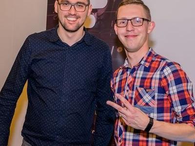 dwaj uśmiechnięci fani zespołu muzycznego