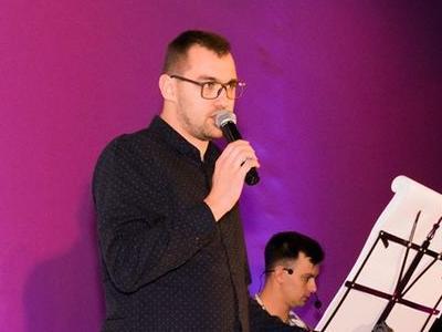 śpiewający przed ciemnoróżową ściana piosenkarz