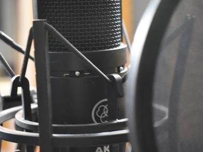 zbliżenie na mikrofon do którego śpiewa piosenkarz w studiu nagraniowym