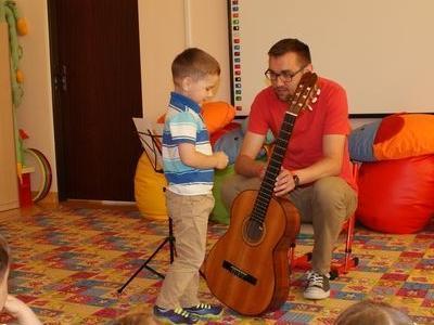 mężczyzna pokazuje małemu chłopcu gitarę