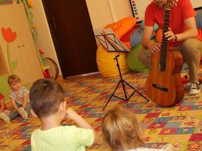 uśmiechnięty mężczyzna uczy grać dzieci na gitarze