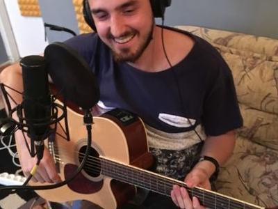 uśmiechnięty solista z gitarą śpiewa do mikrofonu siedząc na sofie