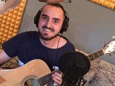 uśmiechnięty solista pozuje do zdjęcia z gitarą