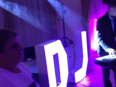 gość stojący obok stanowiska DJ w fioletowej kolorystyce