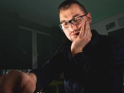 kompozytor siedzący przed swoim stanowiskiem opierając się na swojej lewej dłoni