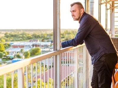 uśmiechnięty mężczyzna rozgląda się z balkonu