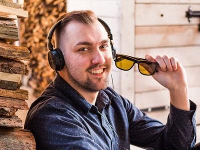 uśmiechnięty mężczyzna ze słuchawkami na głowie i okularami w ręku